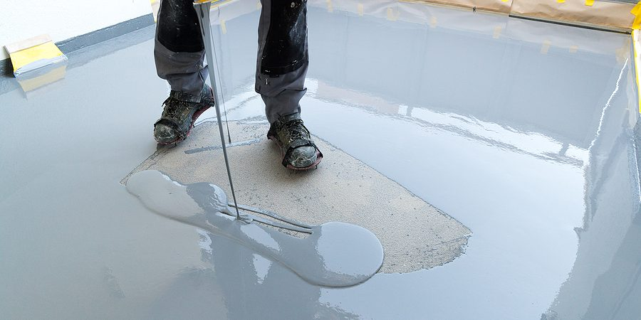 a construction worker renovates balcony floor and spreads watertight resin and glue before chipping and sealing